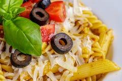 Teigwaren Penne und des fusilli mit Tomaten, Olive, Parmesankäse und Basilikum Lizenzfreie Stockfotografie