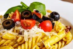 Teigwaren Penne und des fusilli mit Tomaten, Olive, Parmesankäse und Basilikum Lizenzfreies Stockbild