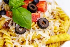 Teigwaren Penne und des fusilli mit Tomaten, Olive, Parmesankäse und Basilikum Stockbild