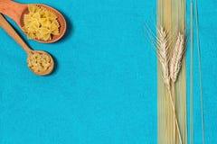 Teigwaren, Spaghettis und Weizen auf einem blauen Hintergrund Stockbilder