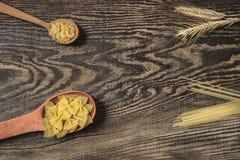 Teigwaren, Spaghettis und Weizen auf einem hölzernen Hintergrund Stockbild