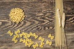 Teigwaren, Spaghettis und Weizen auf einem hölzernen Hintergrund Stockfotos