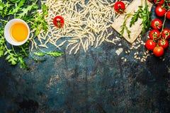 Teigwaren, Tomaten und Bestandteile für das Kochen auf rustikalem Hintergrund, Draufsicht, Grenze Lizenzfreie Stockbilder
