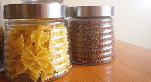 Teigwaren- und bukwheatmahlzeiten Gesundes Kochen in den Glasbehältern auf Holztisch lizenzfreies stockfoto