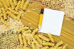 Teigwaren und leeres Papier für Rezept Lizenzfreie Stockfotografie