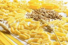 Teigwaren, Weizenzweig und Weizen auf dem Tisch Lizenzfreie Stockfotografie