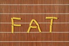 Teigwarenelemente, die Wort FAT auf braunem Tabellensatz bilden Stockfotografie