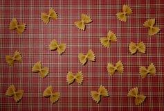 Teigwarenmusterhintergrund Trockenes Vollkorn-farfalle auf roter quadratischer Tischdecke Flache Lage Beschneidungspfad eingeschl Stockbilder