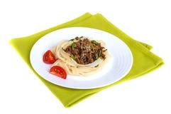 Teigwarennestbandnudeln mit Soße von Bolognese auf einer Platte auf grüner Serviette Lizenzfreie Stockfotos