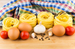 Teigwarennester, -eier und -tomaten auf Hintergrund von Tüchern lizenzfreies stockbild
