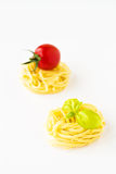 Teigwarennester mit Kirschtomate und -basilikum stockfoto