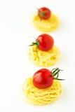 Teigwarennester mit Kirschtomaten stockfoto