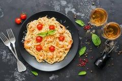 Teigwarenspaghettis mit Garnelen, Tomaten und Weißwein auf einem schwarzen konkreten Hintergrund Ansicht von oben, flache Lage stockfoto