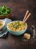 Teigwarenspaghettis mit Spinat Pestosoße, Walnuss und frischen rohen Spinatsblättern in der Schüssel Dunkler Hintergrund Gesunde  stockfotografie