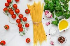 Teigwarenspaghettis mit Tomaten, Knoblauch, Olivenöl und Basilikum auf weißem Marmorhintergrund Bestandteile für italienischen Te Lizenzfreie Stockbilder