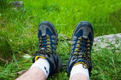 Teil Beine des Mannes In den blauen Trekkingsstiefeln Auf dem gr?nen Gras stockfoto