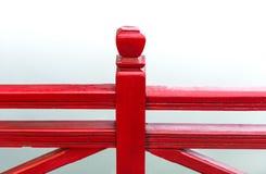 Detail der hölzernen roten Brücke mit Wasserhintergrund. Stockfotografie