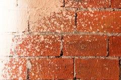 Teil der Wand des roten Backsteins, beschmutzt mit weißer Farbe Stockbild