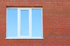Teil der Wand des roten Backsteins und des blauen Fensters mit der Doppelverglasung Stockfoto
