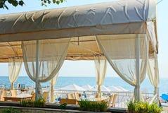 Teil der weißen Veranda des Restaurants mit Vorhängen und Möbeln auf dem Hintergrund des Meeres lizenzfreies stockfoto