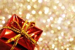 Teil der Weihnachtsroten Geschenkbox mit gelbem Bogen auf Funkelnsilber- und -goldhintergrund Stockfotografie