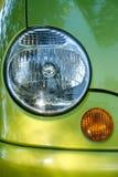 Teil des Autos: Scheinwerfer und Blinker auf grünem Auto Stockfotos
