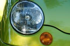 Teil des Autos: Scheinwerfer und Blinker auf grünem Auto Stockbild