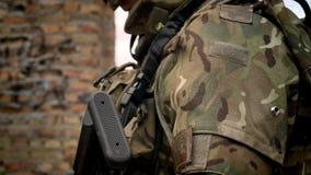 Teil des bewaffneten Soldaten mit Munition und Waffe, stehender nea Backsteinmauerhintergrund, Kriegskonzept stock video