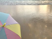 Teil des bunten Pastellregenschirmes auf klarem Sandstrand mit Seewelle lizenzfreies stockfoto