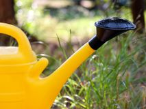Teil des Gartengelbwasserkanisters für Bewässerungsblumen, Gras und Anlagen in der Beschaffenheit des Gartens draußen, Nahaufnahm Stockfotografie