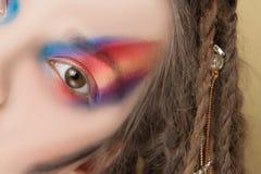 Teil des Gesichtes des Modells mit bunter abstrakter Make-up und Dreadlocksfrisur stockfoto