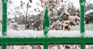 Teil des grünen Eisenzauns, auf den der erste Schnee fiel, Russland Stockfoto
