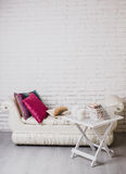 Teil des Innenraums mit Couch und dekorativen Kissen, weißer Holztisch mit Büchern auf ihr Lizenzfreies Stockfoto
