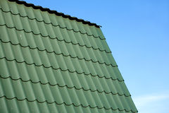 Teil des Landhausdachs von der grünen Metallfliese gegen blauen Himmel Lizenzfreies Stockfoto