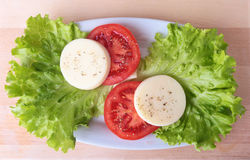 Teil des Mozzarellas mit Tomaten, Kopfsalatblatt und balsamischer Behandlung auf weißer Platte Nahaufnahmeschuß des selektiven Fo Stockbild