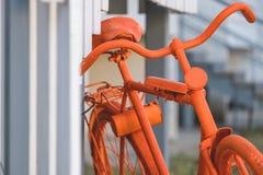 Teil des orange Fahrrades, das nahe der Wand des Hauses und der Treppe steht stockfotografie