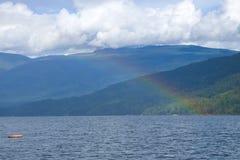 Teil des Regenbogens über dem See Stockfotos