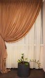 Teil des schön drapierten Vorhangs und der Wand mit Mustern stockfoto