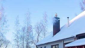 Teil des schneebedeckten Dachs des Hauses mit Kamin, von dem es Rauch gibt stock footage