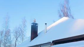 Teil des schneebedeckten Dachs des Hauses mit Kamin, von dem es Rauch gibt stock video footage
