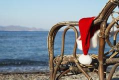 Teil des Stuhls mit Santa Claus-Hut auf Strand Stockbild