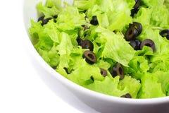 Teil des weißen Tellers mit einem Kopfsalat und Oliven Stockfotografie
