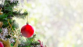 Teil des Weihnachtsbaums mit rotem Weihnachtsball auf grünem und weißem bokeh Hintergrund stockbild