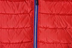 Teil einer rote Männer ` s unten Jacke mit einem blauen Reißverschluss Stockfotos