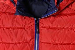 Teil einer rote Männer ` s unten Jacke mit einem blauen Reißverschluss und einem aufgeknöpften Kragen Winteroberbekleidung, struk Lizenzfreies Stockbild