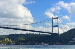 Teil einer Schrägseilbrücke über dem Bosphorus und des Küstenwachebootes am Nachmittag stockfotos