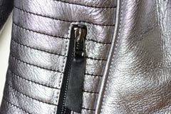 Teil einer silbrigen Jacke mit einem natürlichen Pelzkragen hergestellt vom Schaffell, eine Tasche mit einem Reißverschluss zugem Stockfoto