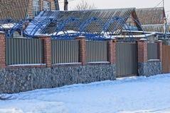 Teil eines braunen Zauns mit geschlossenen Toren auf einer Winterstraße im Schnee Stockfotos