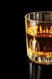 Teil eines Glases mit Alkohol auf einem schwarzen Hintergrund Stockfotografie