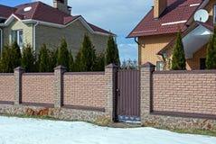 Teil eines langen braunen Ziegelsteinzauns und eine geschlossene Tür an der Straße im Schnee Lizenzfreies Stockfoto